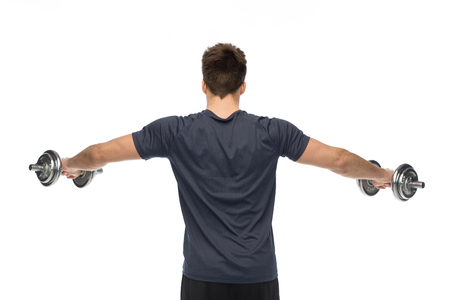 Young man with dumbbells exercising Imagens