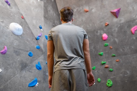 Young man at indoor climbing wall in gym