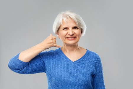 Smiling senior woman making phone calling gesture Banque d'images - 122823024