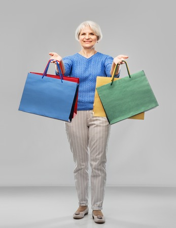 Senior woman with shopping bags over grey background Banque d'images - 122823023