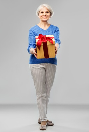 Happy smiling senior woman with birthday gift box Banque d'images - 122823026