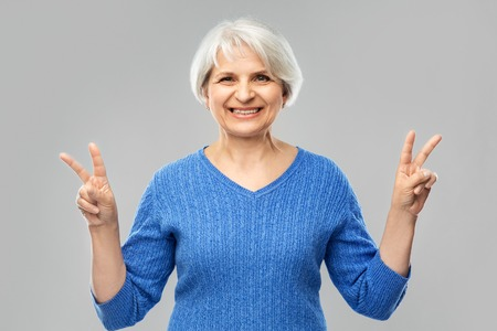 Portrait of smiling senior woman showing peace Banque d'images - 122823073