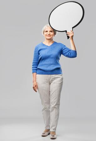 Smiling senior woman holding big speech bubble Imagens