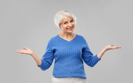 Senior woman shrugging or presenting something