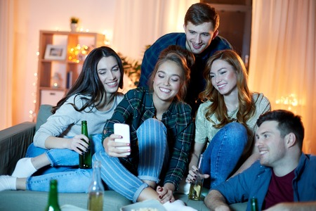 Happy friends with smartphone at home party
