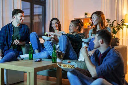 Friends with drinks and snacks watching tv at home Imagens