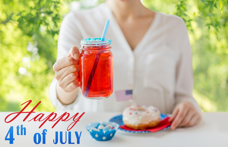 independence day, celebration and holidays concept - close up of woman eating glazed donut, drinking juice from big glass mason jar or mug and celebrating 4th july party over green natural background