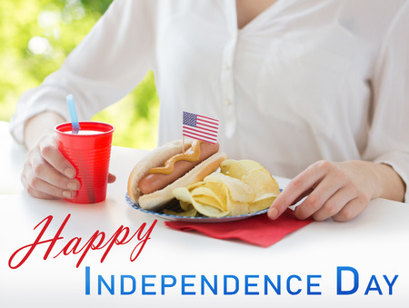 independence day, celebration, patriotism and holidays concept - close up of woman with hot dog decorated by american flag, chips and juice at 4th july party over natural summer green background Stock Photo