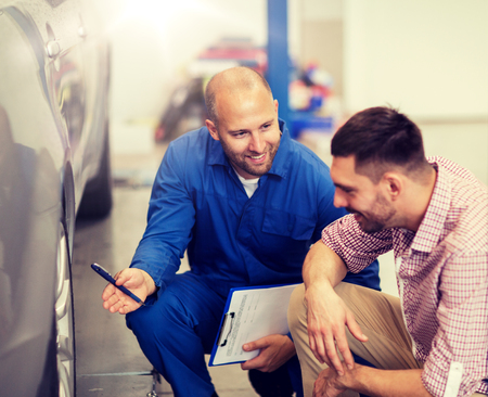 auto service, repair, maintenance and people concept - mechanic with clipboard showing tire to man or owner at car shop 版權商用圖片 - 122978784