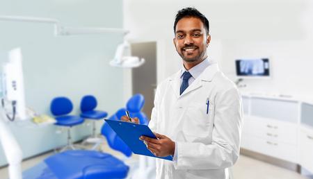 geneeskunde, tandheelkunde en gezondheidszorg concept - lachende Indiase mannelijke tandarts in witte jas met klembord over tandheelkundige kliniek kantoor achtergrond Stockfoto