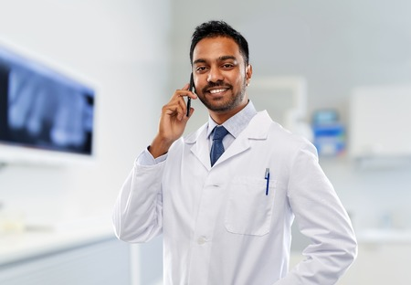medicine, dentistry and healthcare concept - smiling indian male dentist in white coat calling on smartphone over dental clinic office background Stok Fotoğraf