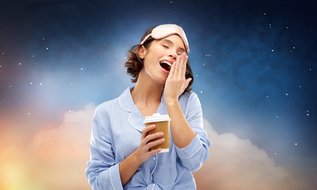 people and bedtime concept - happy young woman in pajama and sleeping mask with paper cup of coffee yawning over starry night sky and cloud background Imagens