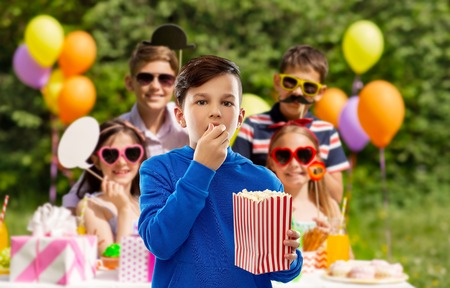 fast food, childhood and people concept - boy in blue hoodie eating popcorn from striped paper bucket over group of friends at birthday party in summer park background Stockfoto