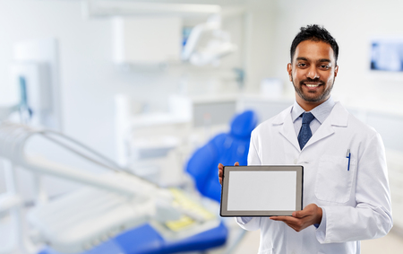 medicine, dentistry and technology concept - smiling indian male dentist in white coat with tablet computer over dental clinic office background Stok Fotoğraf