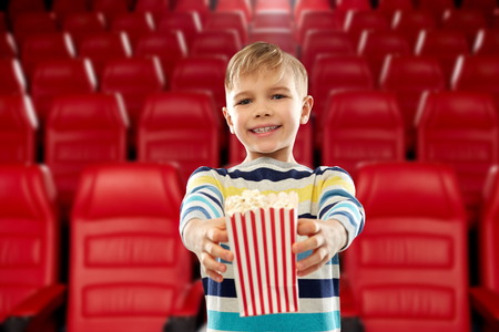 cinema, fast food and entertainment concept - little boy in striped pullover holding paper bucket of popcorn over movie theater background