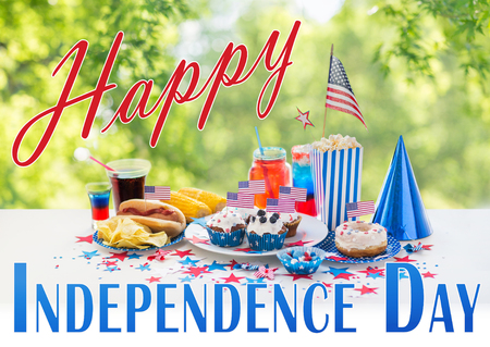 independence day, holidays and celebration concept - close up of hot dog with american flag decoration, potato chips and drinks at 4th july party over green natural background Stock Photo