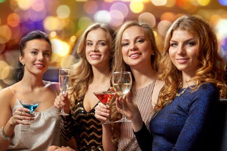 Concepto de celebración, despedida de soltera y vacaciones: mujeres felices o amigas con bebidas no alcohólicas en vasos en el club nocturno Foto de archivo