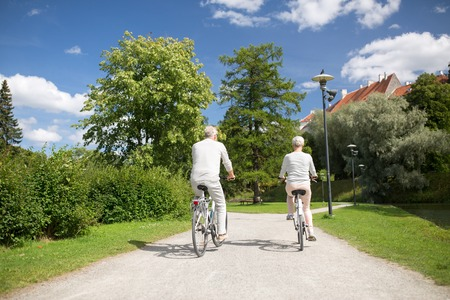 active old age, people and lifestyle concept - happy senior couple riding bicycles at toom park in summer city of tallinn, estonia