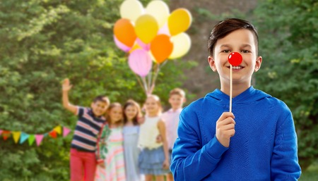red nose day, party props and photo booth concept - smiling boy in blue hoodie with clown nose over group of friends on birthday in summer park background
