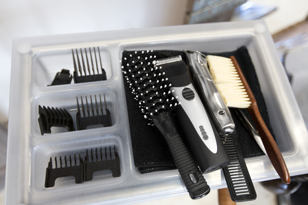 hair tools, grooming and hairdressing concept - brushes, trimmers and comb on tray at barbershop