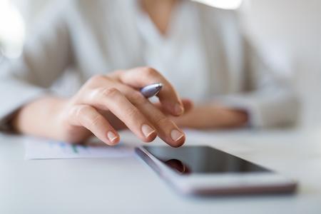 concepto de negocio, tecnología y personas - cerca de la mano de la empresaria con smartphoner en la oficina