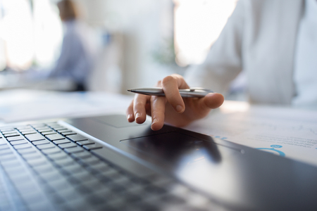 business, people and technology concept - close up of hand of businesswoman with laptop and pen at office