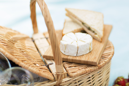 food, eating and leisure concept - brie or camembert cheese and sandwiches on wicker picnic basket Stock fotó - 122979172