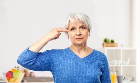 stress, mental health and old people concept - portrait of senior woman in blue sweater making finger gun gesture over kitchen background