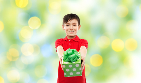 birthday, childhood and people concept - smiling little boy in red polo t-shirt with gift box over green festive lights background Imagens