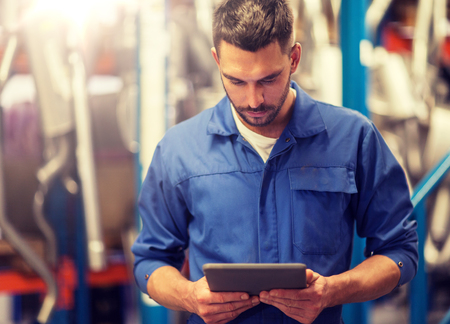car service, repair, maintenance and people concept - auto mechanic man or smith with tablet pc computer at workshop or warehouse Banque d'images