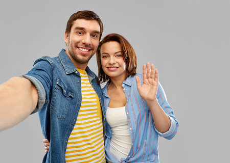 happy couple taking selfie over grey background Stockfoto - 123075118