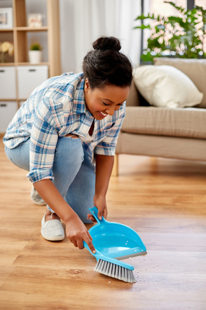 happy woman with brush and dustpan sweeping floor Stockfoto