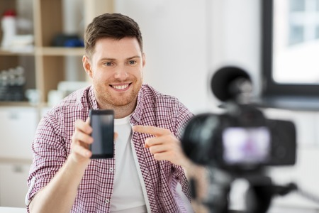 male blogger with smartphone videoblogging at home