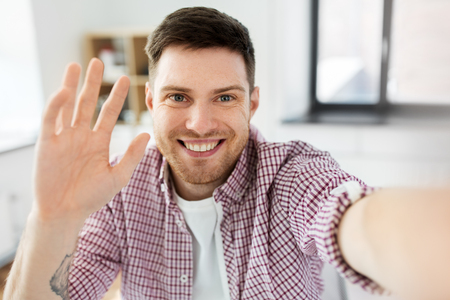 man or video blogger taking selfie and waving hand