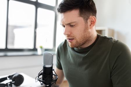 male audio blogger with microphone broadcasting