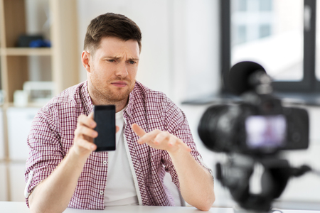 male vlogger with smartphone videoblogging at home