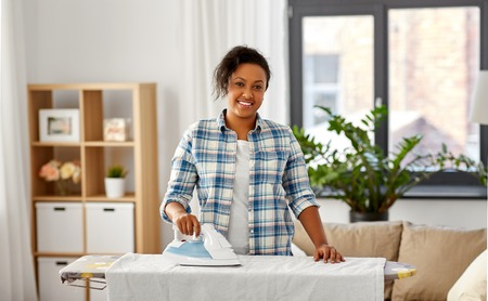 african american woman ironing bed linen at home Archivio Fotografico