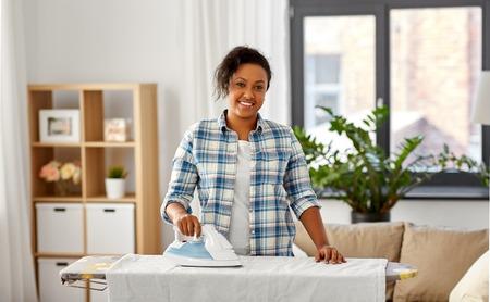 mujer afroamericana, planchar, ropa de cama, en casa