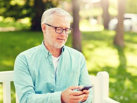 technologie, senioren, levensstijl en communicatieconcept - gelukkige oude man die telefoonnummer kiest en sms't op smartphone in zomerpark