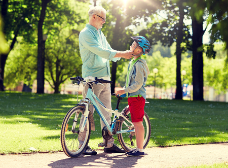 family, generation, safety and people concept - happy grandfather and boy with bicycle and bike helmet at summer park Standard-Bild