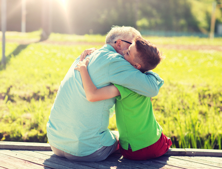 family, generation, communication and people concept - happy grandfather and grandson hugging on berth Stock Photo