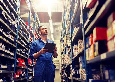 autoservice, reparatie, onderhoud en mensenconcept - automonteur man of smid met tablet pc-computer op zoek naar reserveonderdelen in werkplaats of magazijn Stockfoto