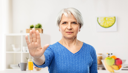 prohibition and old people concept - portrait of senior woman in blue sweater making stop over kitchen background