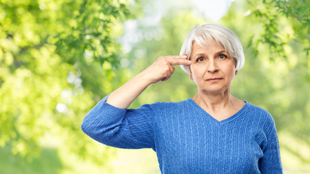 stress, mental health and old people concept - portrait of senior woman in blue sweater making finger gun gesture over green natural background