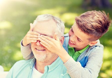 concetto di famiglia, generazione e persone - nonno e nipote felici che giocano a indovinare chi gioca al parco estivo Archivio Fotografico