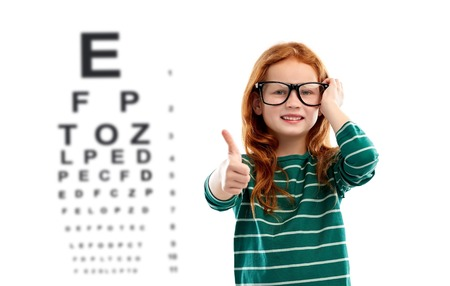 education, vision and childhood concept - smiling red haired student girl in glasses and green striped shirt over eye test chart background