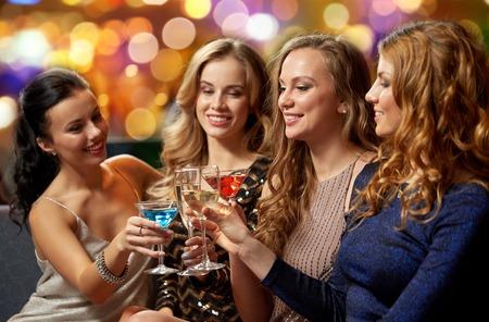 Feier, Junggesellenabschied und Urlaubskonzept - glückliche Frauen oder Freundinnen, die im Nachtclub mit den Gläsern anstoßen