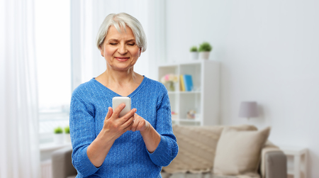 technology and old people concept - smiling senior woman using smartphone over home background 版權商用圖片