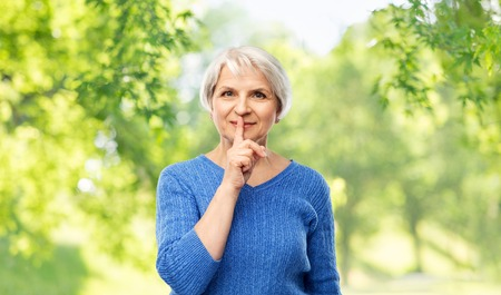 silence, censor and old people concept - portrait of smiling senior woman in blue sweater making shush gesture over green natural background