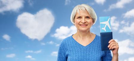 Concepto de turismo, viajes y vacaciones - mujer mayor feliz con pasaporte y boleto de avión sobre fondo de cielo azul y nubes